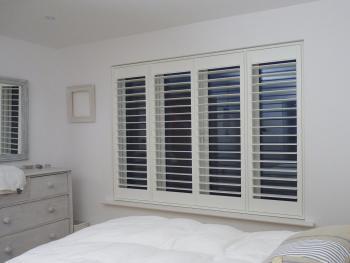 Four Panel White Window Shutters In Bedroom