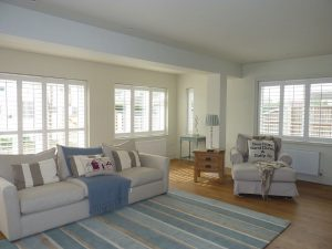 Sea Themed Living Room With White Plantation Shutters At Every Window