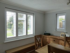 White Plantation Shutters On Two Windows In Dining Room