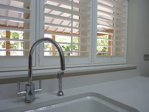 White Shutter Blinds Behind Kitchen Sink