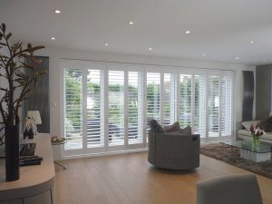White Plantation Shutters On Track Across Patio Doors