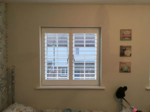 White Plantation Shutters On Small Square Window In Bedroom