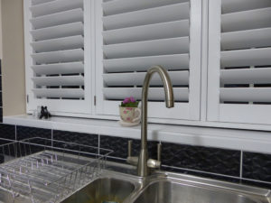 White Shutters On Window Above Sink In Kitchen