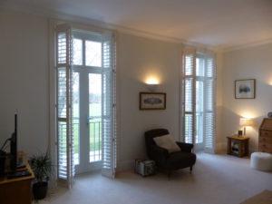 White Shutter Blinds On Tall Living Room Doors