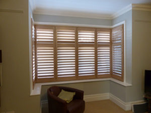 Stained Wooden Shutters In Square Bay Window