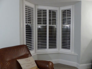 White Louvered Shutters In Angled Bay Window
