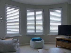 White Plantation Shutters In Three angled Windows In Lounge