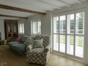White Wooden Shutters On Patio Doors And Two Windows