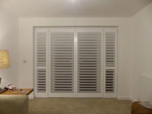 White Wooden Shutters On Living Room Doors