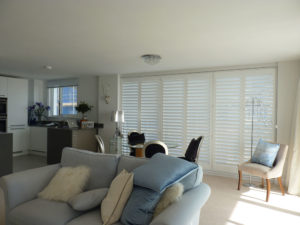 White Wooden Shutters On Living Room Patio Doors