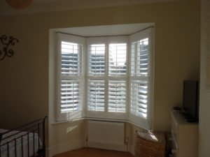 White Shutters On Angled Bay Window In Bedroom