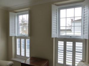 Two White Top Opening Tier On Tier Window Shutters