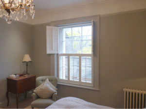 White Tier On Tier Shutters With Top Panels Open In Bedroom