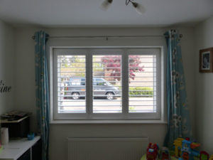 White Plantation Shutters With TPosts In Child's Bedroom