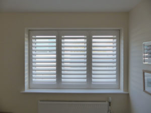 White TPost Shutters In Three Panel Window