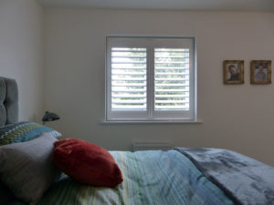 White Wooden Shutters In Small Bedroom Window