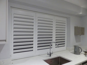 White Shutters In Three Panel Window Above Kitchen Sink