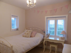 White Louvered Shutters In Girl's Bedroom
