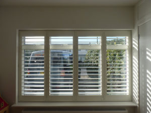 Cream Shutters In Four Panel Window