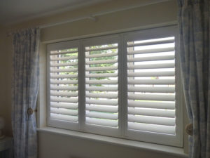 White Shutter Blinds With TPosts And Curtains Either Side