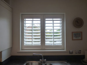 White Shutters In Small Kitchen Window Above Sink